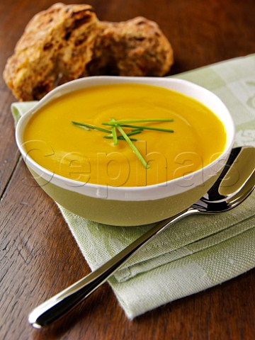 Bowl of pumpkin soup with brown bread rolls