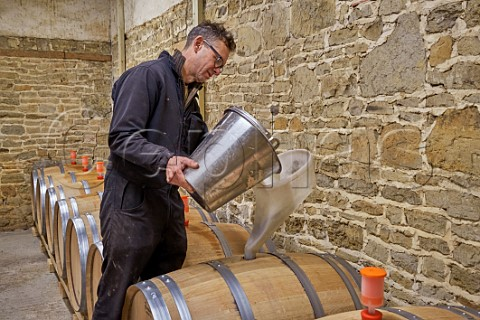 Simon Woodhead winemaker filling new oak barrel with Chardonnay must in winery of Stopham Estate Stopham Sussex England